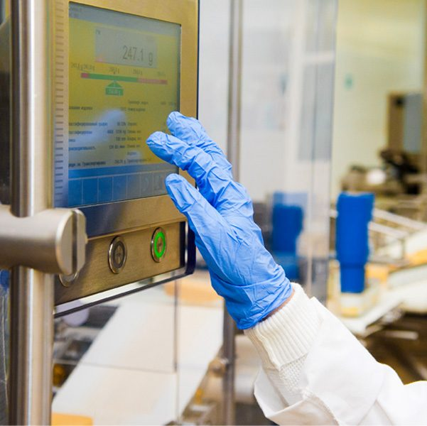 Gloved right hand and forearm of team member about to touch a touch screen on cheese production machine